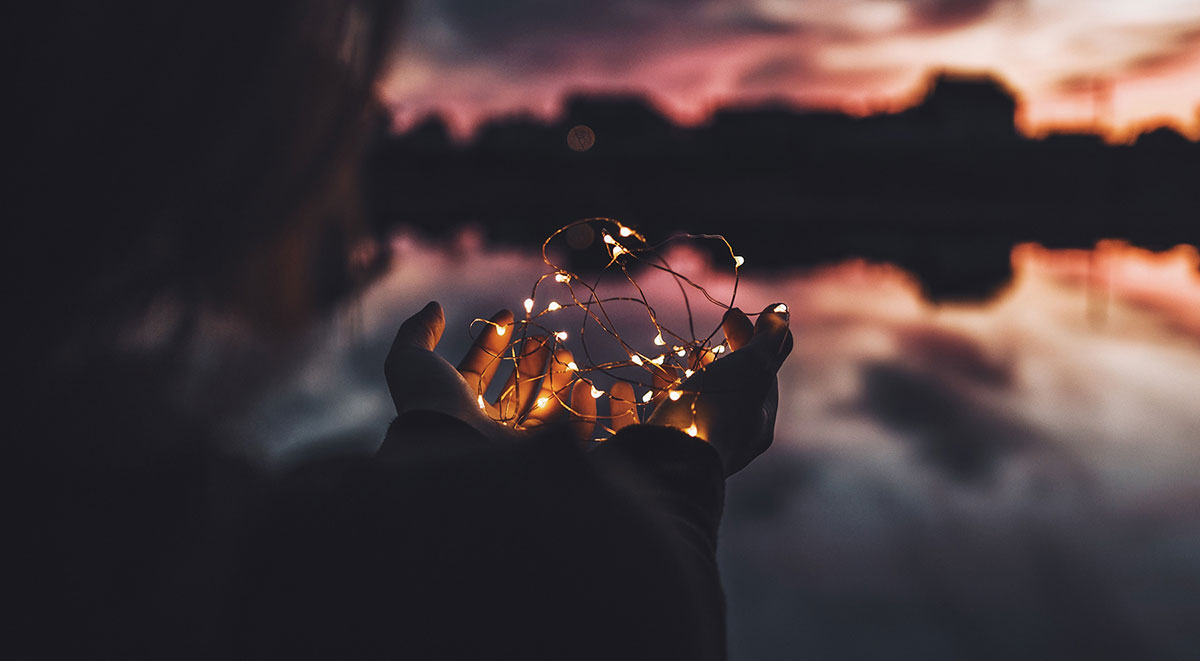 Woman's hands holding small string of lights overlooking a warm sunset that is reflected in a lake in front of her.