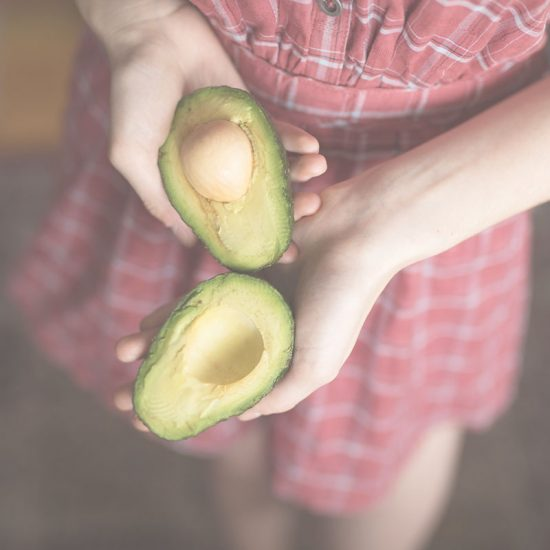 Thin woman in pink dress holding avocados