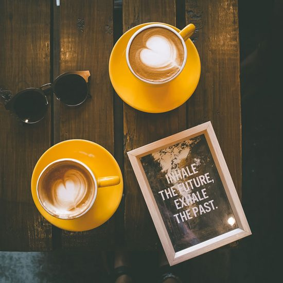 Two cups of coffee with frame that reads: Inhale the Future, Exhale the Past